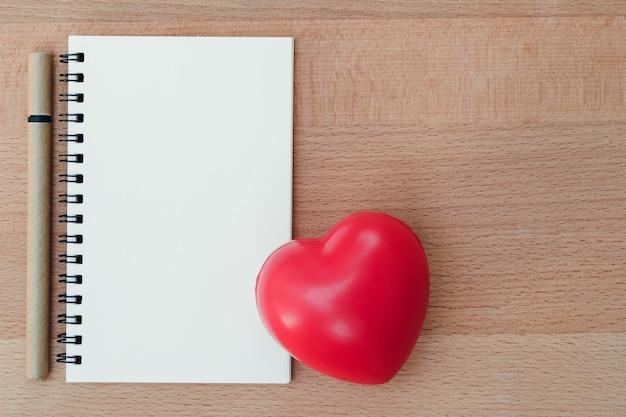 Nota en blanco con materiales de escritura y símbolo de corazón rojo en madera, utilizando como fondo