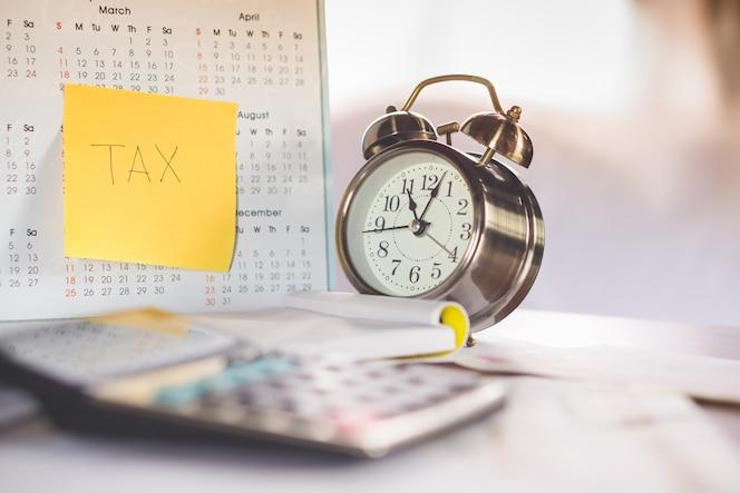 Nota de la palabra de impuestos en el calendario, reloj despertador y calculadora en la tabla, concepto de tiempo de impuestos