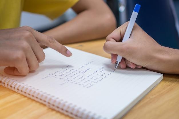 Nota del estudiante asiático en el cuaderno mientras aprende a estudiar y escribir para planificar estudiar