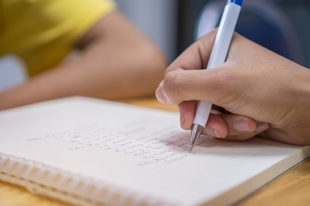 Nota del estudiante asiático en el cuaderno mientras aprende a estudiar y escribir para el trabajo de planificación.