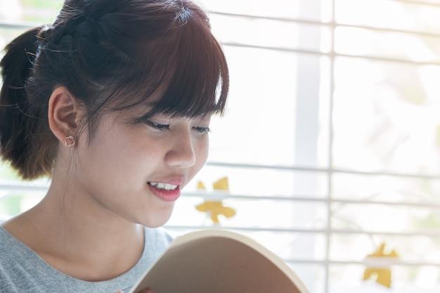 Nota del estudiante asiático en el cuaderno mientras aprende a estudiar y leer en línea para planificar el trabajo