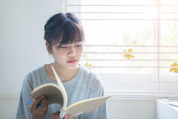Nota del estudiante asiático en el cuaderno mientras aprende el estudio en línea o el aprendizaje electrónico a través de una computadora portátil
