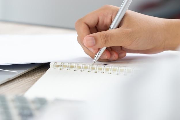 Nota de estudiante asiático en el cuaderno mientras aprende estudio en línea