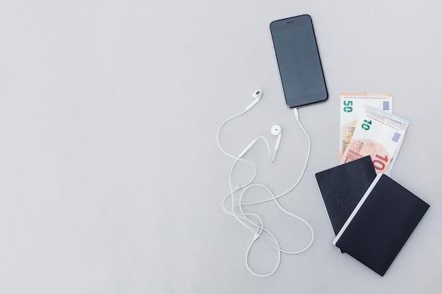 Nota de moneda en el pasaporte con teléfono móvil y auriculares en fondo gris
