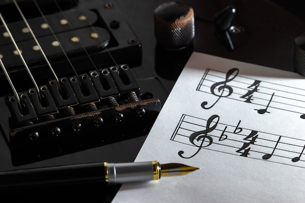 Nota musical y pluma vintage en guitarra eléctrica negra en la oscuridad.