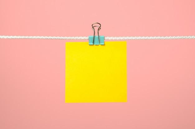 Nota de papel amarillo en blanco en la cuerda