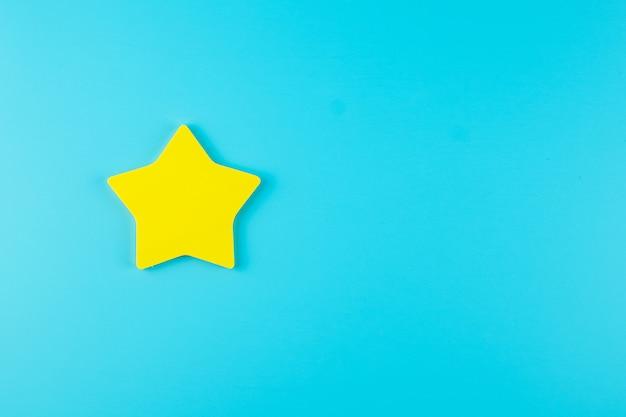 Una nota de papel amarillo estrella sobre fondo azul con espacio de copia de texto. comentarios de los clientes, comentarios, calificación, clasificación y concepto de servicio.