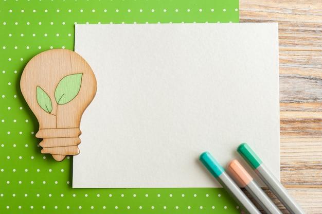 Nota de papel en blanco y lámpara de madera y lápices.