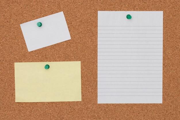 Nota de papel con el pasador en fondo del tablero del corcho.