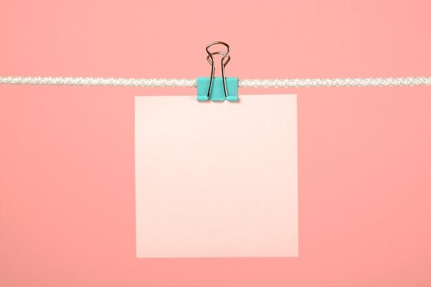 Nota de papel rosa en blanco sobre tendedero