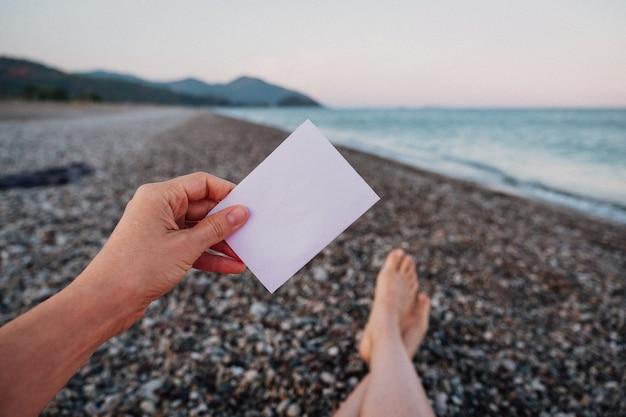 Nota de papel vacía en la mano en el fondo del paisaje increíble
