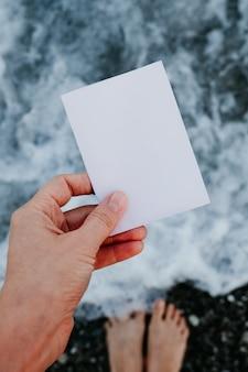 Nota de papel vacía en la mano en un paisaje increíble