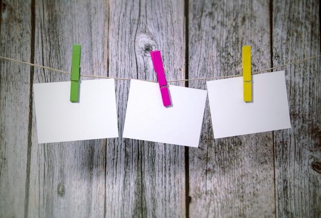 Nota papeles colgando de una cuerda sobre madera