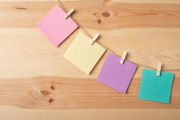 Nota papeles de diferente color en hilo contra mesa de madera