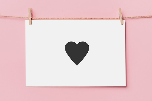Nota pin de letra en cuerda sobre fondo rosa, amor y concepto de san valentín con corazón