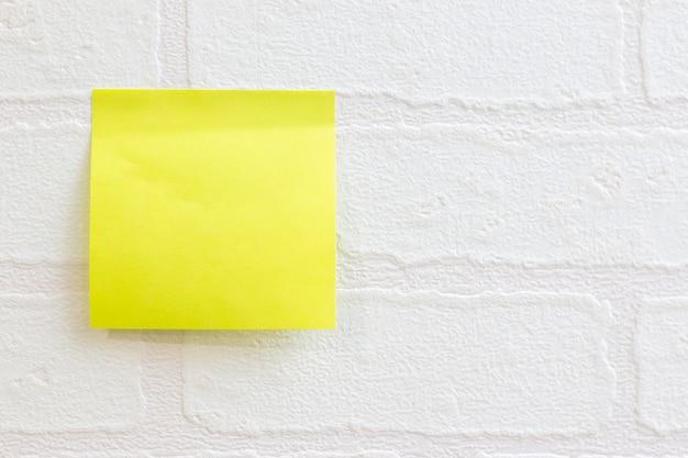 Nota de post-it o nota adhesiva sobre el uso del patrón de ladrillo de papel tapiz blanco para el fondo