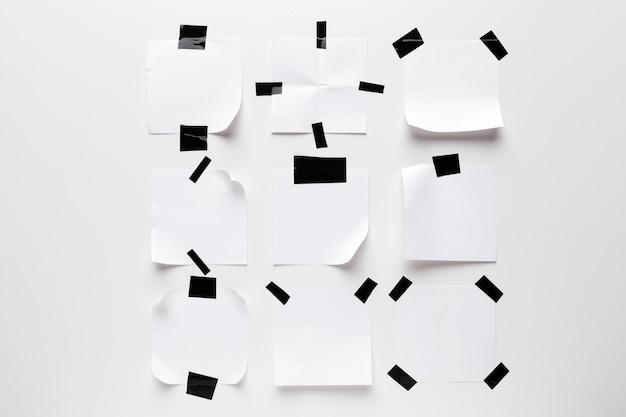 Nota rasgada blanca, papel de cuaderno pegado con cinta adhesiva negra aislada sobre fondo blanco