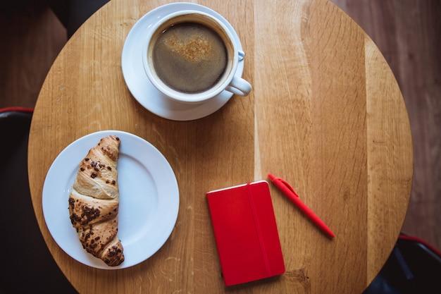 Una nota roja y un bolígrafo rojo sobre la mesa en un café, una taza de café y un cruasán