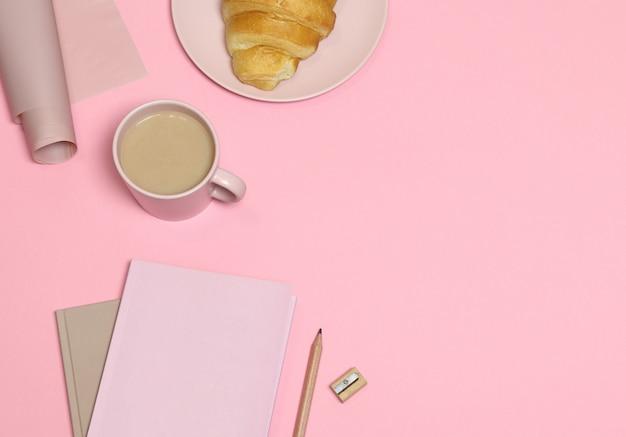 Nota rosa con lápiz y sacapuntas, taza de café, pastel sobre fondo rosa