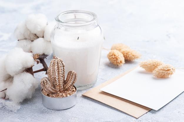 Nota vacía y sobre kraft. flor de algodón y vela en botella de vidrio sobre fondo de hormigón blanco