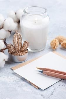 Nota vacía y sobre kraft con lápices. flor de algodón y vela en botella de vidrio sobre fondo de hormigón blanco