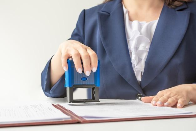 Notario oficial poniendo sello en los documentos. en una chaqueta azul