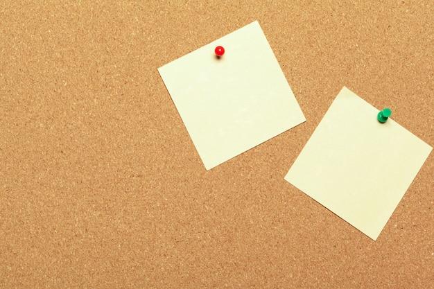 Notas adhesivas blancas con chinchetas en la superficie del corcho