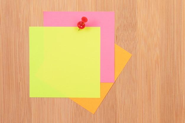 Notas adhesivas de colores clavadas en el tablero de mensajes de madera