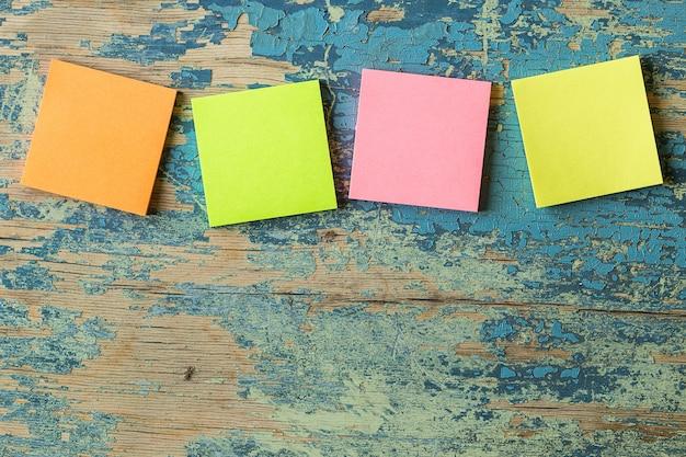 Notas adhesivas de colores en madera rústica.