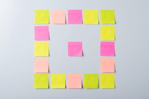Notas adhesivas de diferentes colores en forma de cuadrado sobre una pared gris.