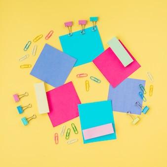 Notas adhesivas multicoloras y sujetapapeles en superficie amarilla