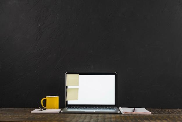 Notas adhesivas pegadas en la computadora portátil cerca de la taza y el bloc de notas en superficie de madera