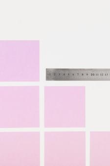 Notas adhesivas rosas y regla sobre fondo blanco
