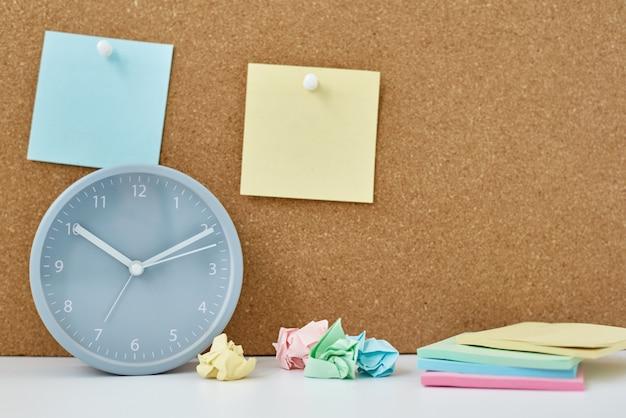 Notas adhesivas en el tablero de corcho y reloj despertador en la oficina o en el hogar