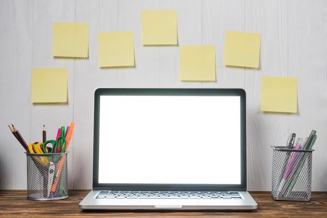 Notas adhesivas y papelería cerca de la computadora portátil