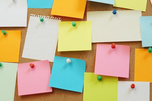 Notas apestosas en blanco pin en el tablero de corcho. tablero de corcho con notas en blanco.