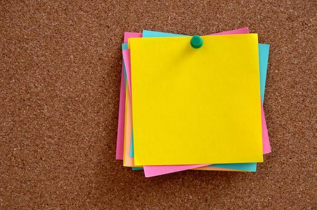 Notas en blanco clavadas en panel de corcho marrón