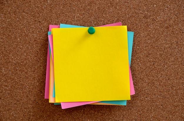 Notas en blanco clavadas en el panel de corcho marrón