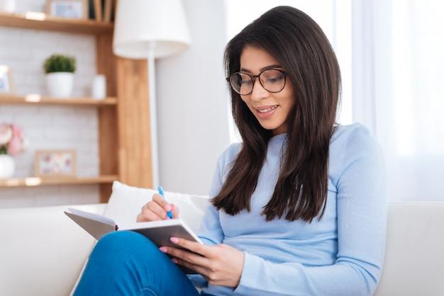 Notas detalladas. estudiante alegre alegre con gafas mientras anota notas