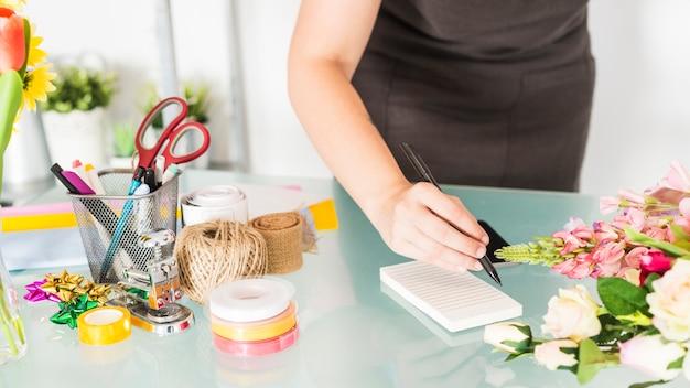 Notas de la escritura de la mano de la mujer en la libreta sobre el escritorio de cristal