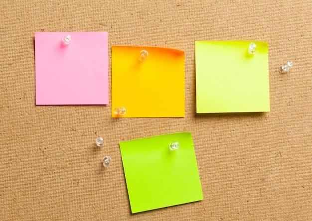 Notas de la etiqueta de color sobre fondo de tablero de corcho