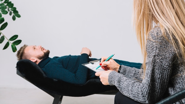 Notas femeninas de la escritura del psicólogo en el tablero delante del paciente que miente en el sofá en clínica