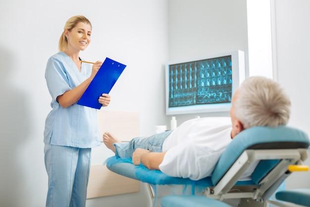 Notas de los médicos. feliz mujer amable positiva mirando a su paciente y sonriendo mientras toma notas