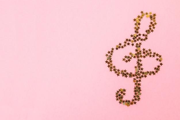 Notas musicales de confeti dorado estrellado sobre un fondo rosa pastel.