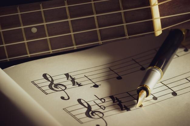 Notas musicales y libro antiguo sobre mesa de madera