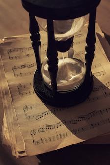 Notas musicales sobre papeles y reloj de arena.