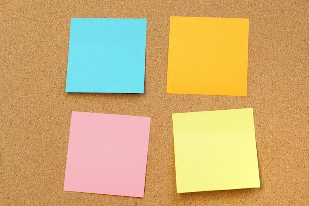 Notas de papel en blanco se pegan en el tablero de corcho tablero de corcho con post-it en blanco