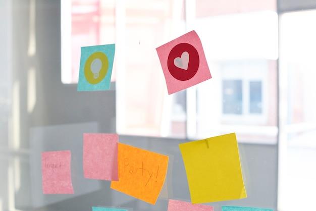Notas recordatorias de notas adhesivas cosidas en la oficina de pared de cristal