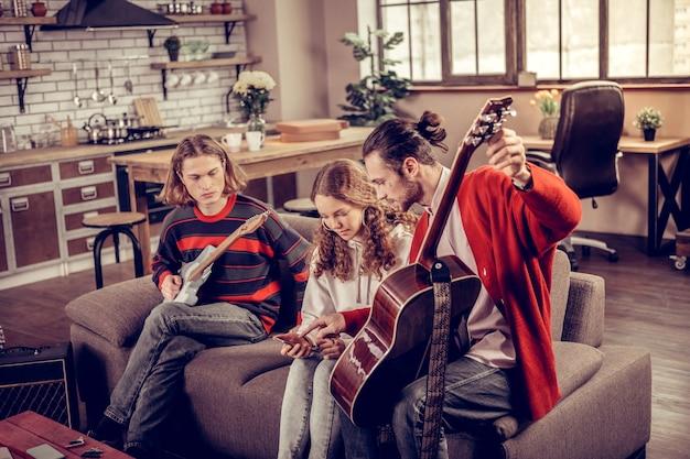 Notas sobre el teléfono. tutor de guitarra de pelo oscuro barbudo enseñando a adolescente mostrando sus notas musicales en el teléfono