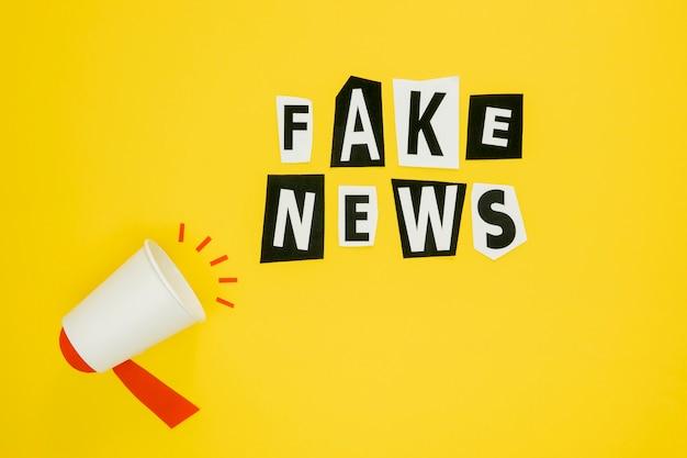 Noticias falsas y megáfono sobre fondo amarillo